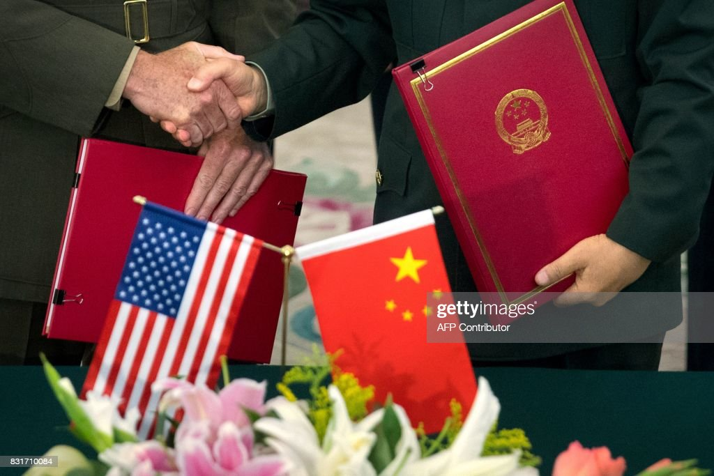 General Joseph Dunford (L), chairman of the US Joint Chiefs of Staff, and Chief of the General Staff of the Chinese People's Liberation Army General Fang Fenghui shake hands after signing an agreement at the Bayi Building in Beijing on August 15, 2017. / AFP PHOTO / POOL / Mark Schiefelbein