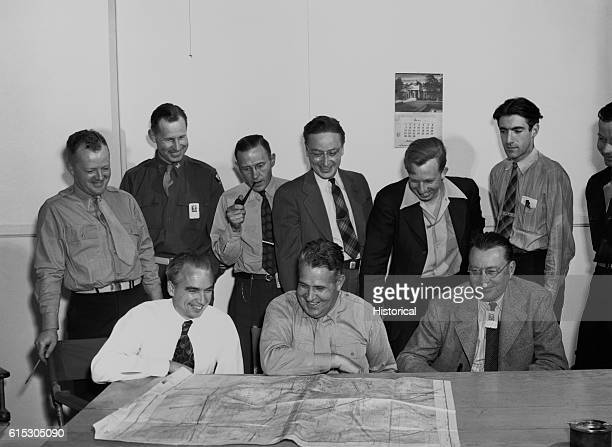 General Leslie Groves commander of the Manhattan Engineers District better known as the Manhattan Project looks over a map with members of the...