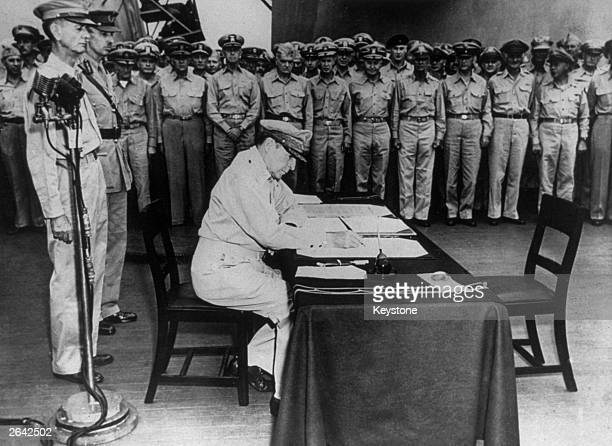 General MacArthur signs the Japanese surrender document on board the USS Missouri in Tokyo Harbour Amongst those standing behind are Lieutenant...