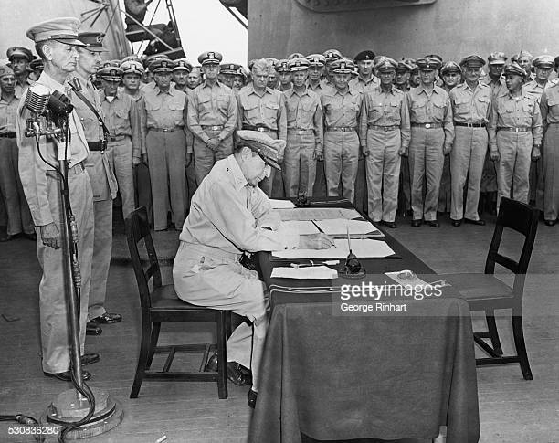 General MacArthur signs the surrender papers aboard the USS Missouri on September 2 1945 Standing behind him are Lieutenant Generals Johathan...