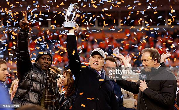 General Manager and Executive Vice President of Football Operation for the Denver Broncos John Elway holds up the Lamar Hunt Trophy with former...