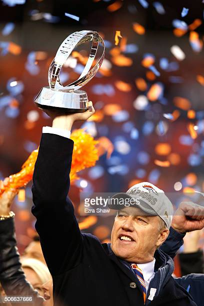 General Manager and Executive Vice President of Football Operation for the Denver Broncos John Elway holds up the Lamar Hunt Trophy after defeating...