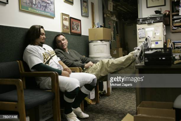 General Manager Billy Beane and Nick Swisher of the Oakland Athletics talk in the clubhouse before the game against the San Francisco Giants at the...