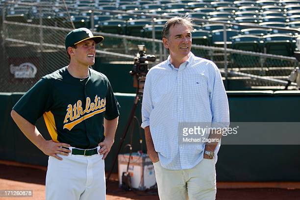 General Manager Billy Beane of Oakland Athletics talks with the team first round draft pick Billy McKinney during a workout prior to the game against...