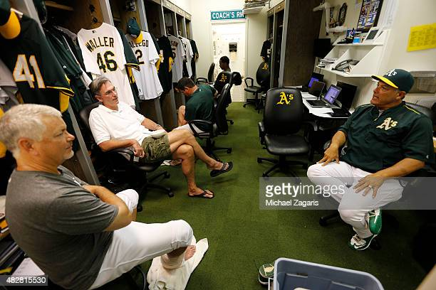 General Manager Billy Beane of the Oakland Athletics talks with Pitching Coach Curt Young and Bench Coach Mike Aldrete in the clubhouse prior...