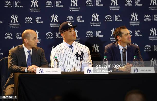 General Manager Brian Cashman Giancarlo Stanton and Manager Aaron Boone are seen during a press conference where Stanton is introduced as a member of...