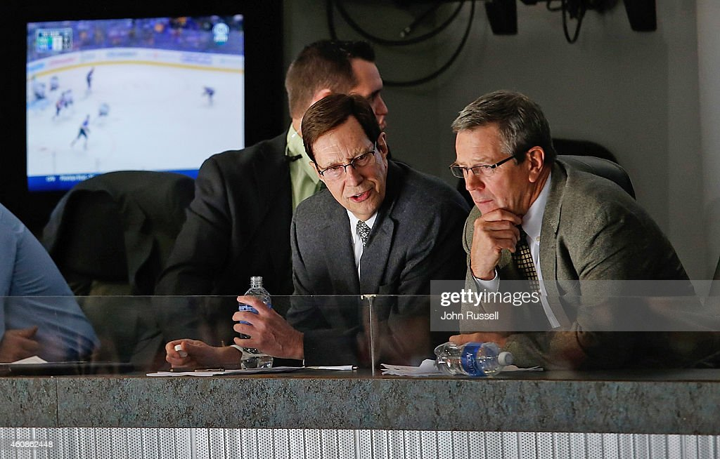 General manager David Poile talks with assistant gm Paul Fenton of the Nashville Predators during the second period of a game against the Philadelphia Flyers at Bridgestone Arena on December 27, 2014 in Nashville, Tennessee.