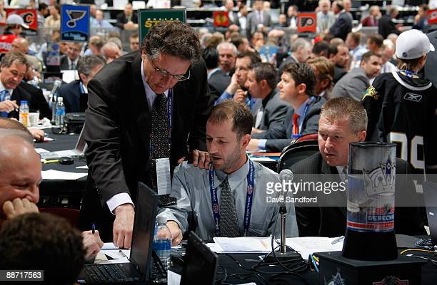 General Manager Dean Lombardi of the Los Angeles Kings confers with scouts Mark Yannetti and Michael Futa during the second day of the 2009 NHL Entry...
