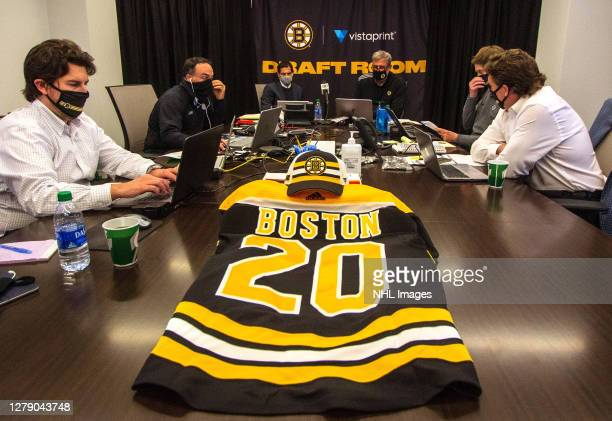 General manager Don Sweeney president Cam Neely and Boston Bruins team personnel sit at the draft table during the first round of the 2020 NHL Entry...