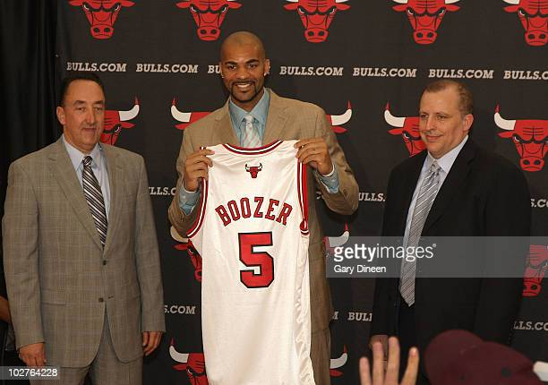 General Manager Gar Forman Carlos Boozer and Head Coach Tom Thibodeau of the Chicago Bulls pose for a photograph following Boozer's signing as a free...