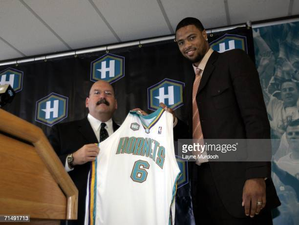General Manager Jeff Bower of the New Orleans/Oklahoma City Hornets presents his new player Tyson Chandler with his jersey during a press conference...