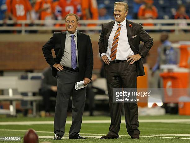 General Manager John Elway Denver Broncos and broadcaster Al Michaels look on from the field prior to a gave between the Denver Broncos and Detroit...