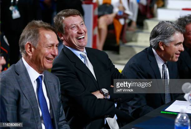 General manager Ken Holland executive Wayne Gretzky and head coach Dave Tippett of the Edmonton Oilers laugh at the team draft table during the first...