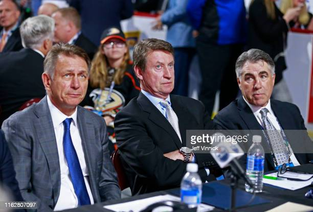General manager Ken Holland executive Wayne Gretzky and head coach Dave Tippett of the Edmonton Oilers look on from the team draft table during the...