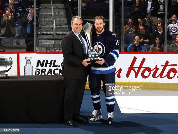 General Manager Kevin Cheveldayoff of the Winnipeg Jets presents Bryan Little with the Dan Snyder Memorial Award prior to NHL action against the...
