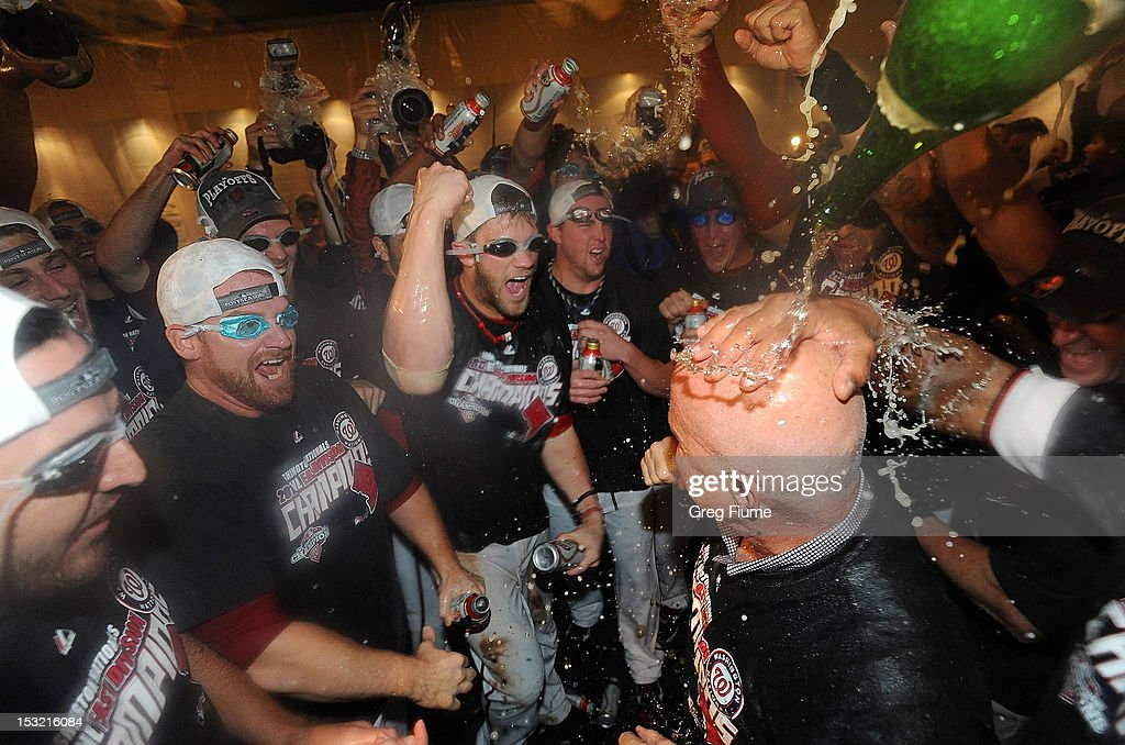 General manager Mike Rizzo is doused with champagne as the Washington Nationals celebrate after winning the National League East Division Championship after the game against the Philadelphia Phillies at Nationals Park on October 1, 2012 in Washington, DC.