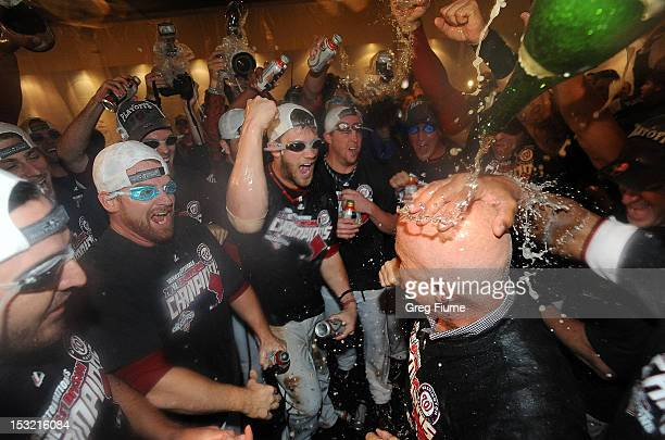 General manager Mike Rizzo is doused with champagne as the Washington Nationals celebrate after winning the National League East Division...