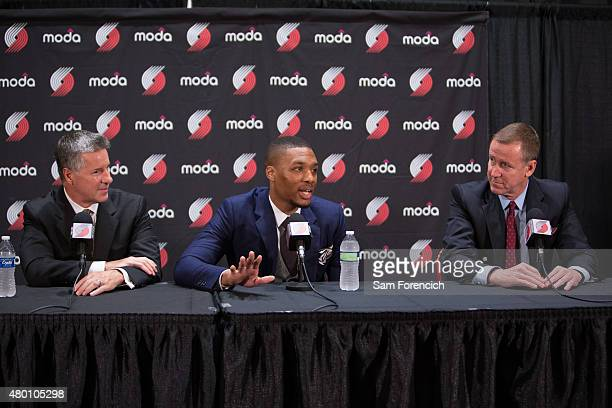 General Manager Neil Olshey and Head Coach Terry Stotts look on as Damian Lillard of the Portland Trail Blazers speaks with the media after signing a...