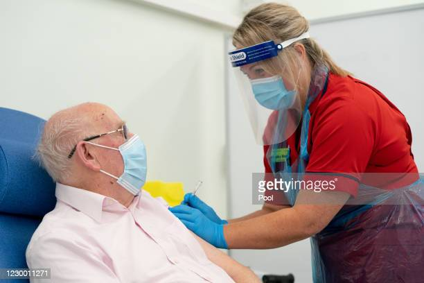 General manager of Covid Recovery, Becky Board, prepares to administer the first Pfizer-BioNTech COVID-19 vaccine in London to patient George Dyer at...