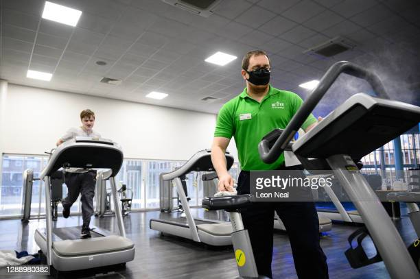 General Manager of Kensington Leisure Centre Martin Marshall cleans gym equipment as a man runs on a treadmill on the first day of re-opening after...