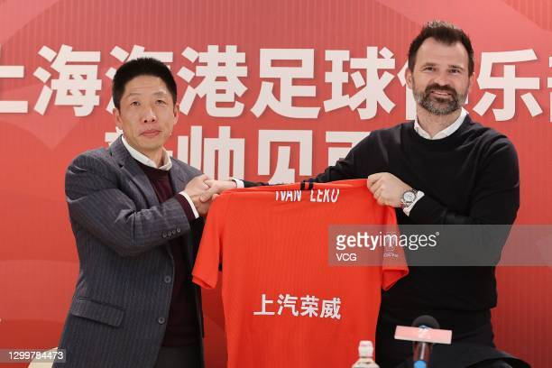General manager of Shanghai Port Football Club Zhang Min shakes hands with new head coach of Shanghai Port Football Club Ivan Leko during a press...