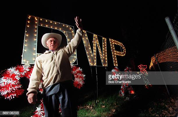 General Manager of the L.A. Department of Water and Power S. David Freeman waves at passing motorists at east end of 'Festival of Lights' display at...