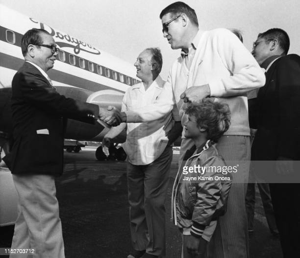 General manager of the Tokyo Giants Kenta Hasegawa is greeted by manager Tommy Lasorda and President Peter O'Malley of the Los Angeles Dodgers as...