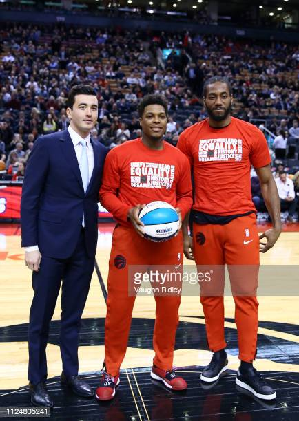 General Manager of the Toronto Raptors Bobby Webster presents an AllStar ball to Kyle Lowry and Kawhi Leonard prior to an NBA game against the...