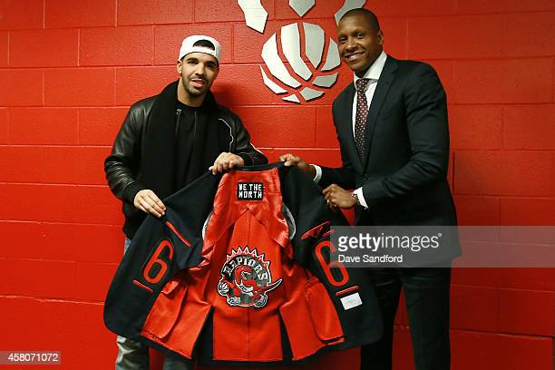 General Manager of the Toronto Raptors Masai Ujiri presents and musician Drake with a Toronto Raptors jacket during their NBA game at the Air Canada...