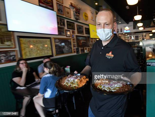 General manager Steven Hanson carries food to a table at Hussong's Cantina in Boca Park Fashion Village as some businesses that were closed seven...