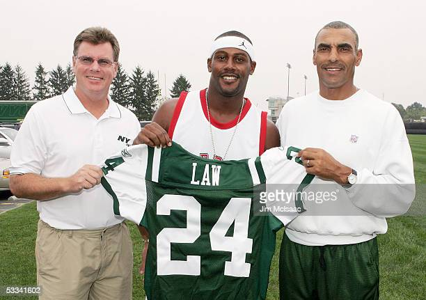 General manager Terry Bradway and head coach Herman Edwards present the newest member of the New York Jets Ty Law his jersey after speaking to the...