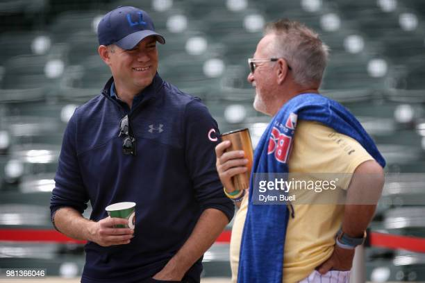 General manager Theo Epstein and manager Joe Maddon of the Chicago Cubs meet before the game against the Los Angeles Dodgers at Wrigley Field on June...
