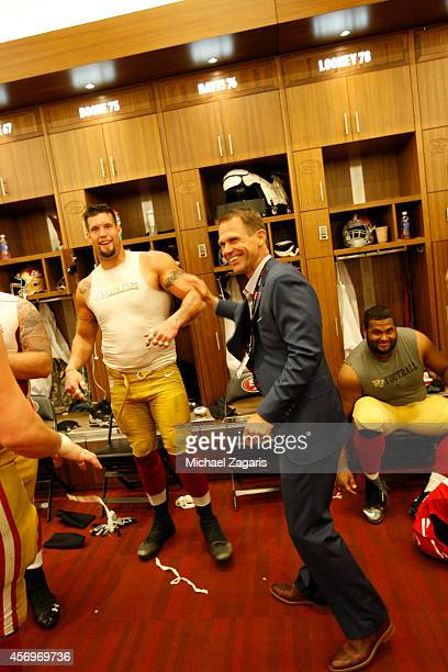 General Manager Trent Baalke of the San Francisco 49ers congratulates Alex Boone in the locker room following the game against the Kansas City Chiefs...