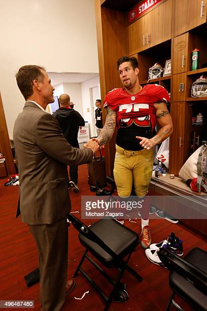 General Manager Trent Baalke of the San Francisco 49ers congratulates Alex Boone in the locker room following the game against the Atlanta Falcons at...