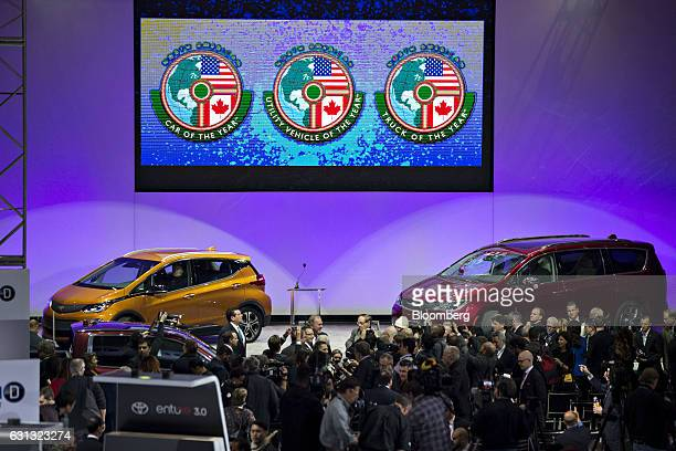 A General Motors Co Chevrolet Bolt EV left and Fiat Chrysler Automobiles NV Pacifica sit on display after winning the 2017 Car of the Year during the...