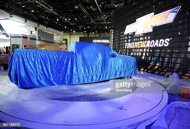 A General Motors Co Chevrolet model truck is covered by a tarp during a media walkthrough ahead of the 2015 North American International Auto Show at...