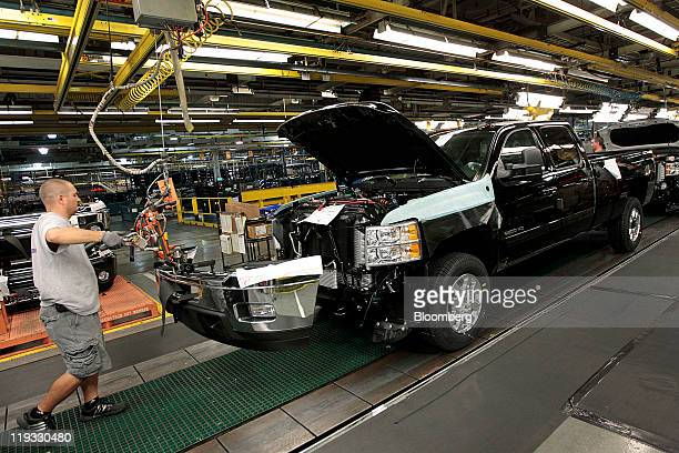General Motors Co. Employee Anthony McMillen installs the front bumper on a GMC Sierra truck at company's assembly plant in Flint, Michigan, U.S., on...