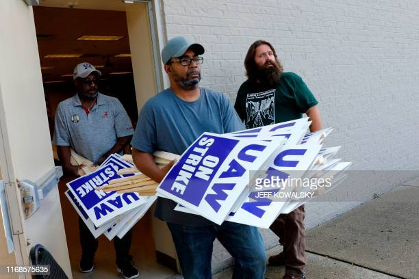 TOPSHOT General Motors Co employee Carl Ellison carries strike signs outside of the United Auto Workers Local 163 which represents GMs Romulus...