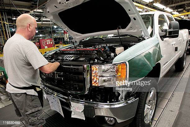 General Motors Co. Employee Les Little installs the front grill on a GMC Sierra truck at company's assembly plant in Flint, Michigan, U.S., on...