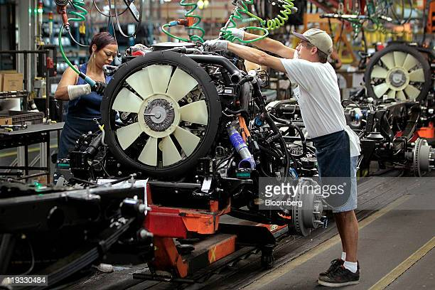 General Motors Co. Employee Mark Fulcher, right, works on the line at the company's assembly plant in Flint, Michigan, U.S., on Monday, July 18,...
