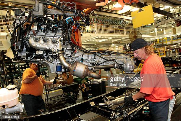 General Motors Co. Employees Lim Sommerville, left, and Steve Welch work on the line at the company's assembly plant in Flint, Michigan, U.S., on...