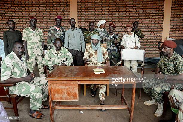 General Moussa C looking at his phone flanked by soldiers poses on July 25 2013 at the Bangui firefighters barracks turned into a Seleka base The...