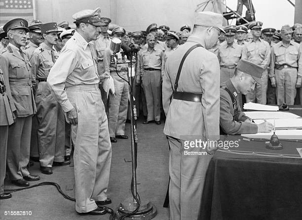 General of the Army Douglas MacArthur watches as Chinese representative General Hsu Yungchang signs a peace treaty during official ceremonies of...