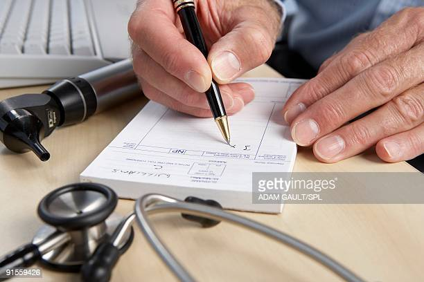 General practice doctor writing prescription