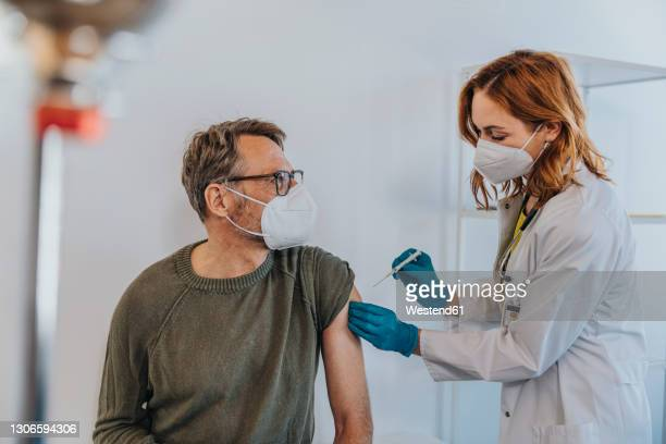 general practitioner injecting covid-19 vaccine in patient arm while standing at examination room - hausarzt stock-fotos und bilder