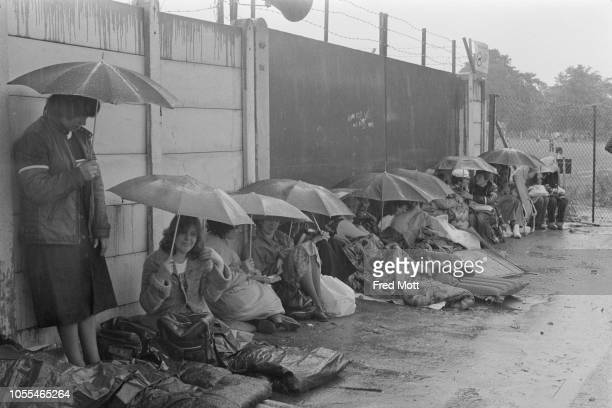 General public queuing up to attend Wimbledon Championships while they wait under the pouring rain, London, UK, 25th June 1979.