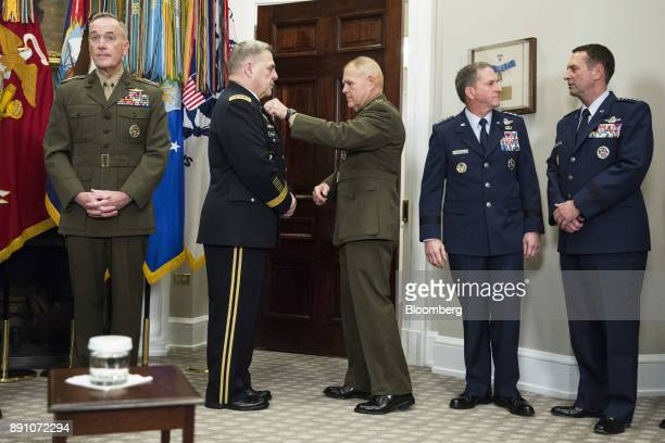 General Robert Neller commandant of the US Marine Corps center adjusts the uniform of General Mark Milley chief of staff with the US Army before US...