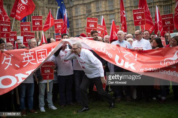 General Secretary of Unite the Union Len McCluskey ducks under a banner as he joins Honda employees as they stage a protest over the planned closure...
