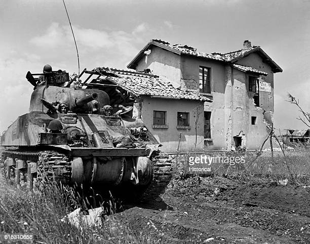 General Sherman tank passes by a destroyed home on the way to the front lines in Italy June 10 1944