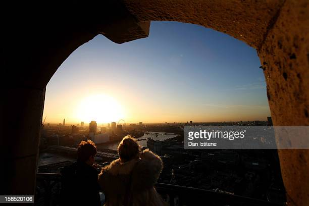 A general view across London at sunset as a sightseer takes a photograph from the Golden Gallery at St Paul's Cathedral towards the River Thames and...